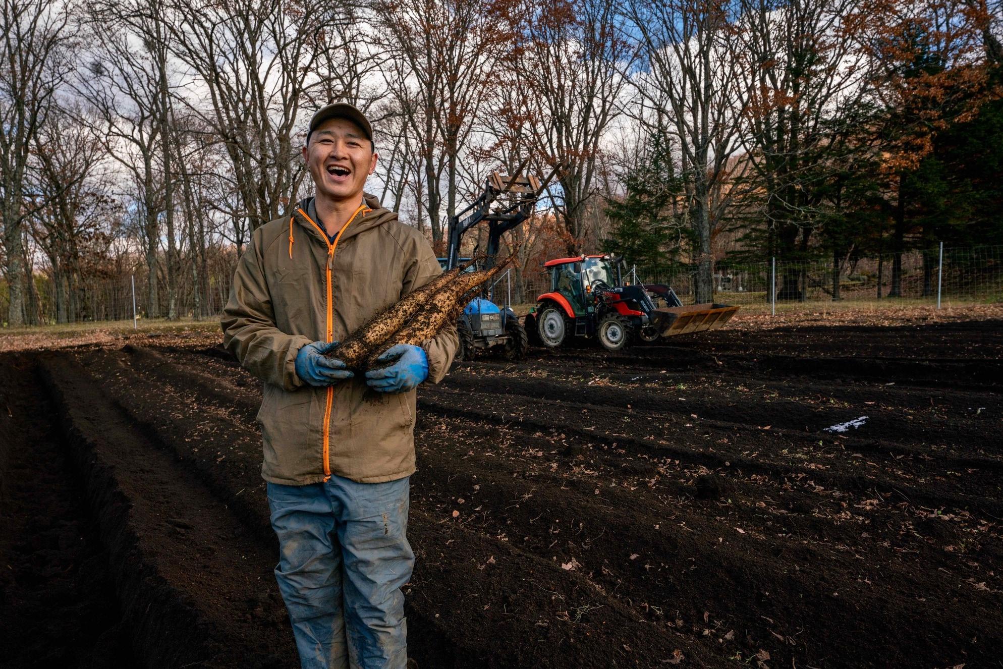 北海道むかわ町穂別の四代目中澤農園,だるまいも畑で長芋を持ち笑顔の中澤さん