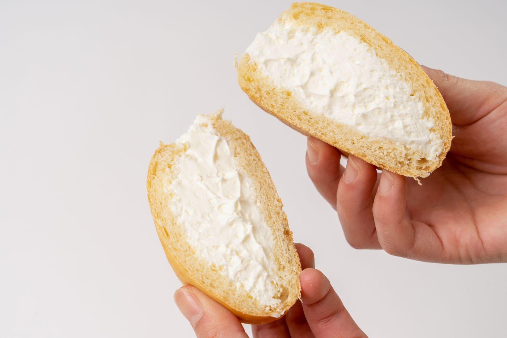 北海道産の純生クリームがたっぷり詰まったSUVACOのクリームパンを手で割る