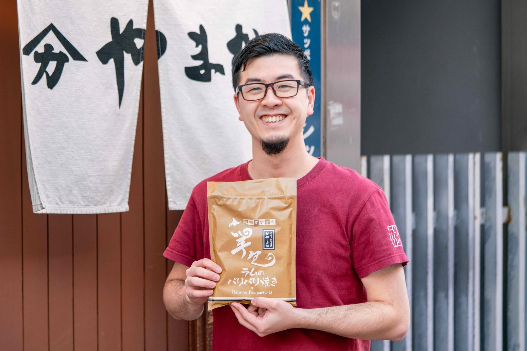 北海道札幌市すすきのの炭焼きジンギスカン専門店やまか,店の暖簾の前でオリジナル商品のラムのパリパリ焼きを持つ佐藤さん