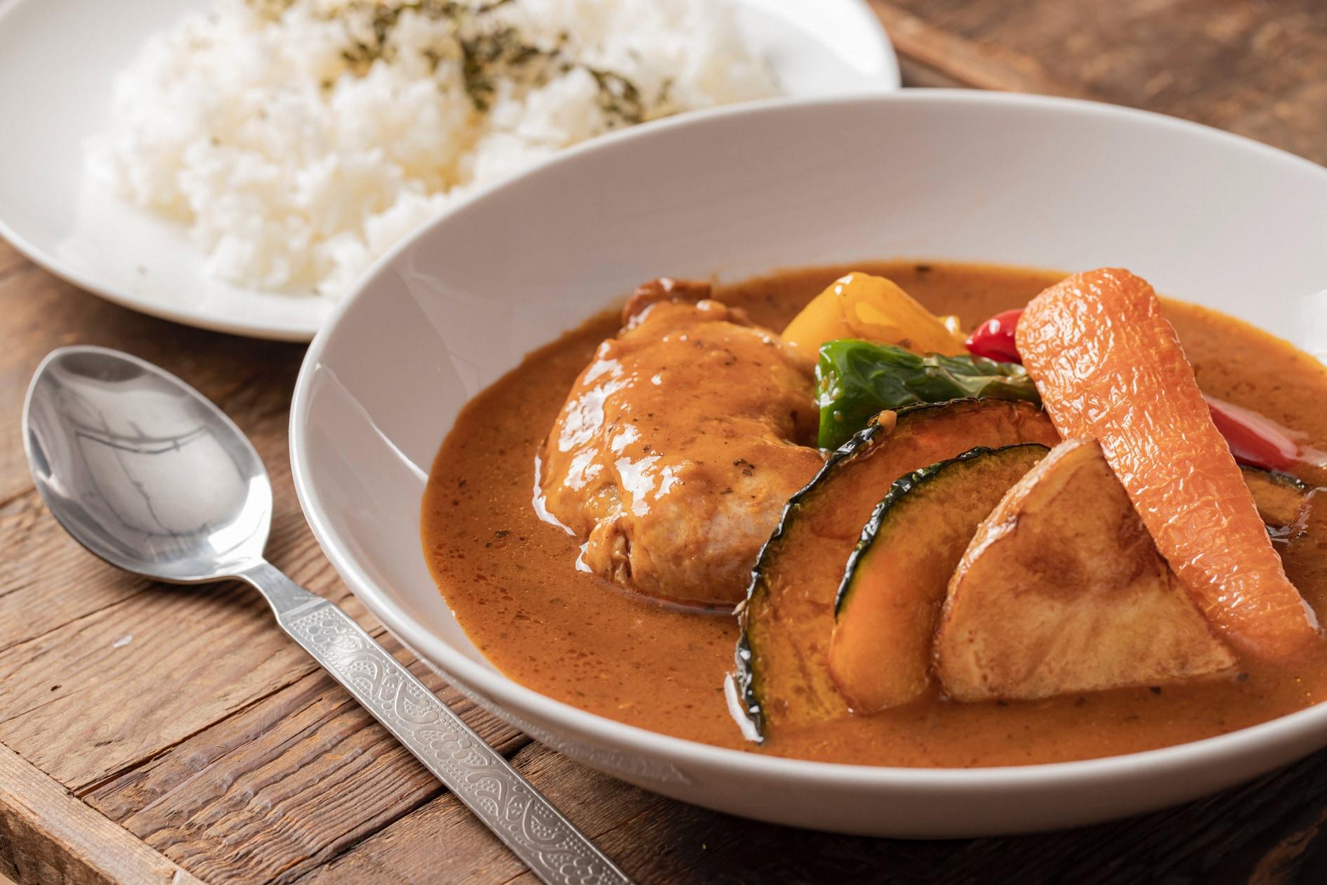 スープカリィ侍のレトルト商品「骨付きチキンのスープカレー」を調理して皿に盛り付ける,具材たっぷりのスープカレー・ライス・スプーン
