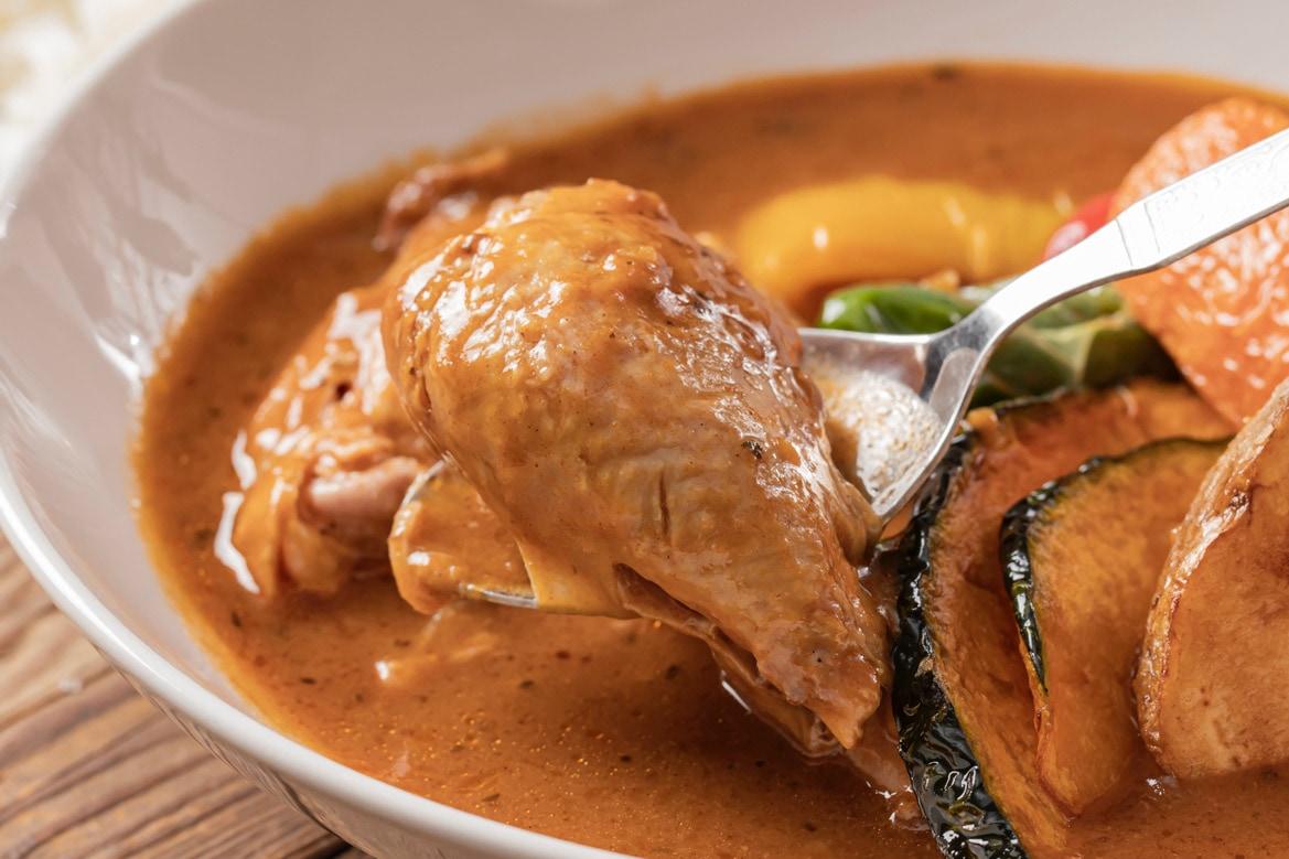 札幌路地裏スープカリィ侍のチキンレッグをスプーンで持ち上げる,SAMURAI.レトルト「骨付きチキンのスープカレー」