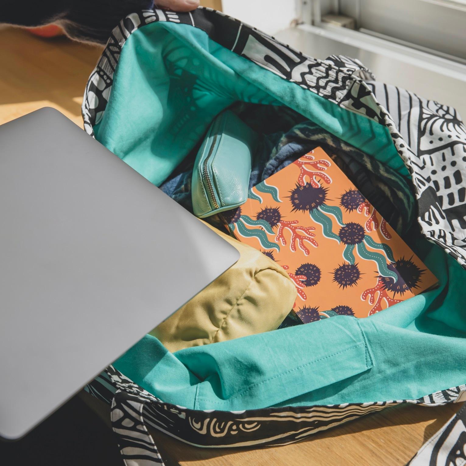 内側にアオ色の生地が使用されたmonmecci(モンメッチ)の大きな幾何学模様バッグ