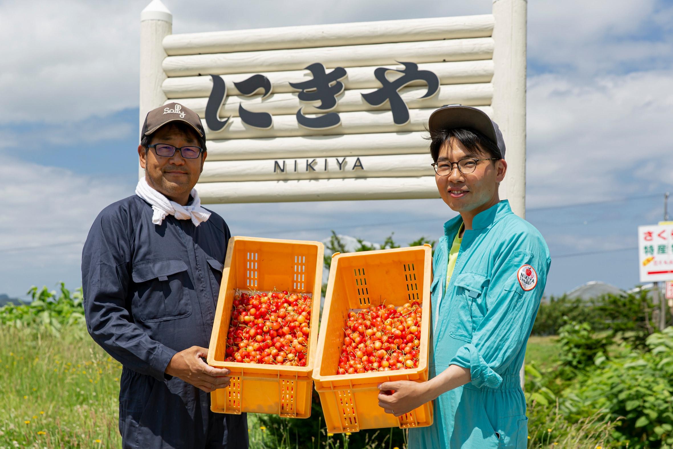 NIKIYA FARM & BREWERY -にきや-の看板の前に立つ小林さんと大木さん