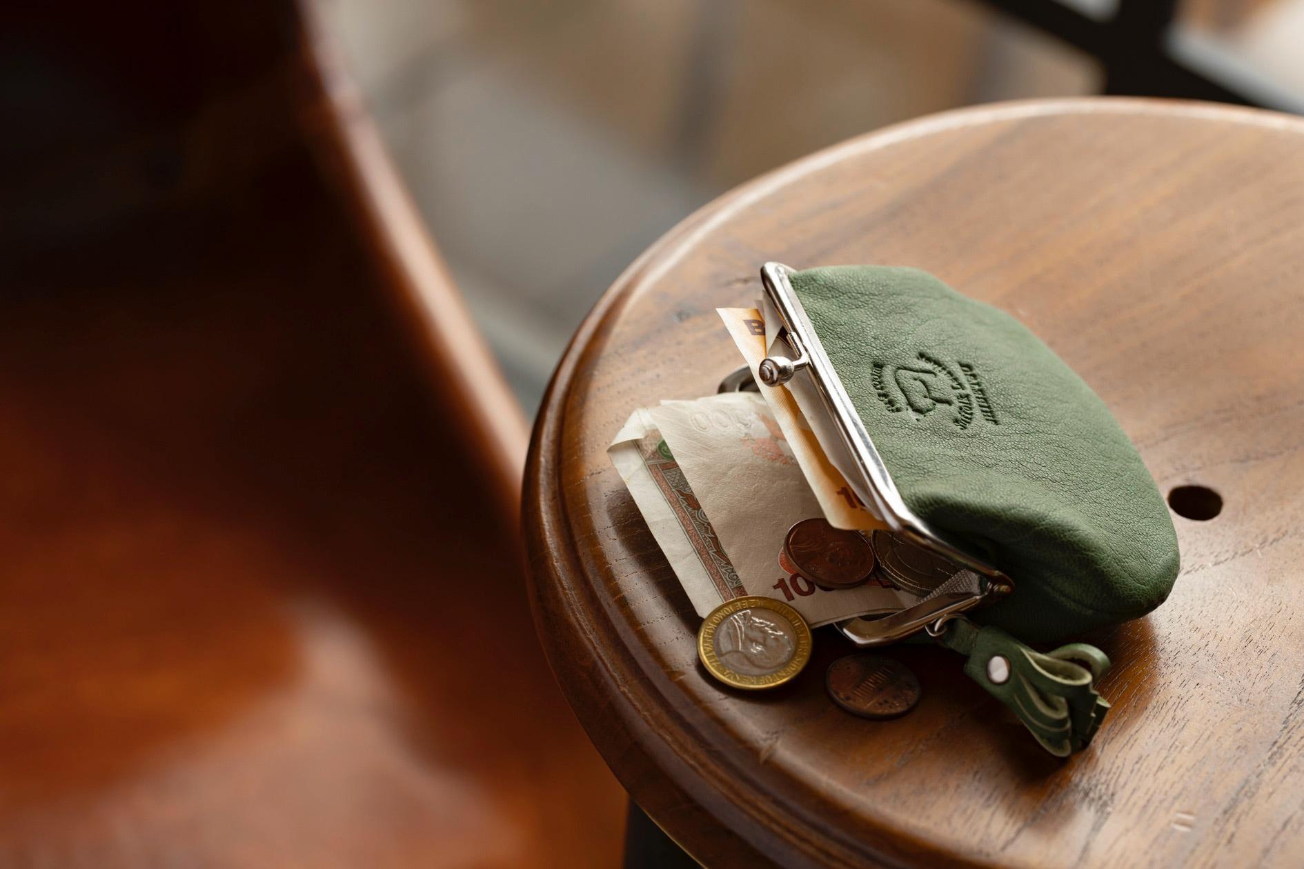 テーブルの上に置かれたFu's roomのサフォークレザーの「がま口(Mサイズ)」とお札とコイン,ハンドメイドクラフト