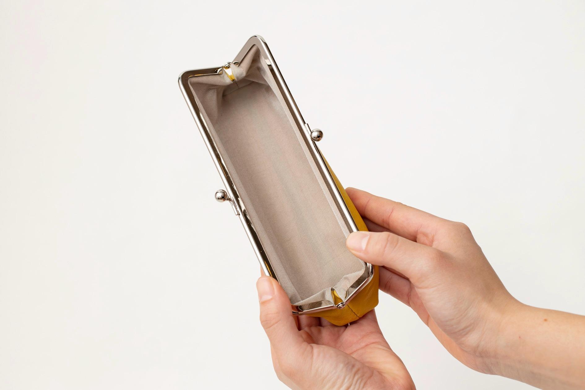 Fu's roomのレモン色のサフォークレザー「がま口(ロングサイズ)」を開いて見せる