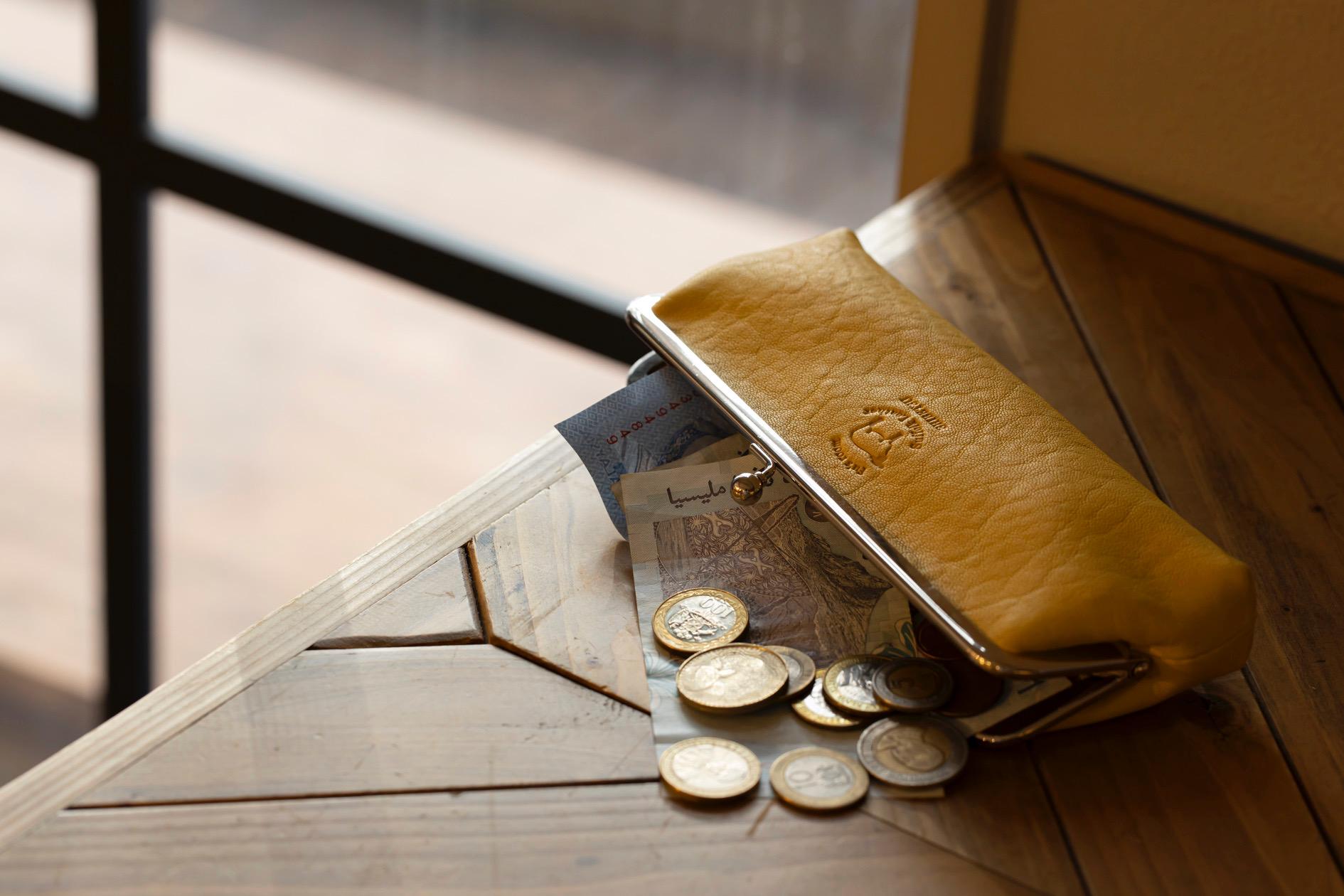 テーブルの上に置いたFu's roomのサフォークレザーのがま口とお札とコイン