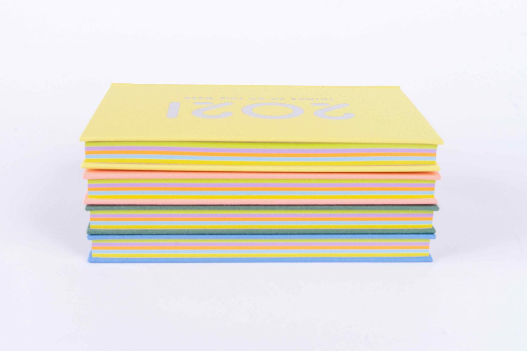 石田製本のboocoダイアリー4冊を積む,スケジュール帳のカラフルな本紙が見える状態