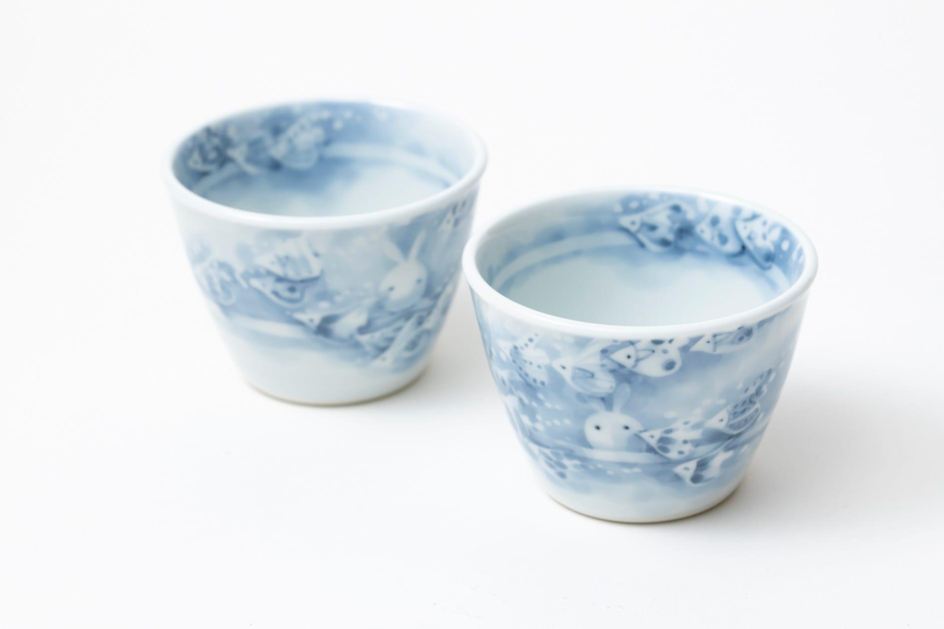 描かれたうさぎや魚の表情が一つずつ異なる黒羽陶工房の2つのフリーカップ(すいぞくかん),淡いブルーの濃淡が特徴のカップ