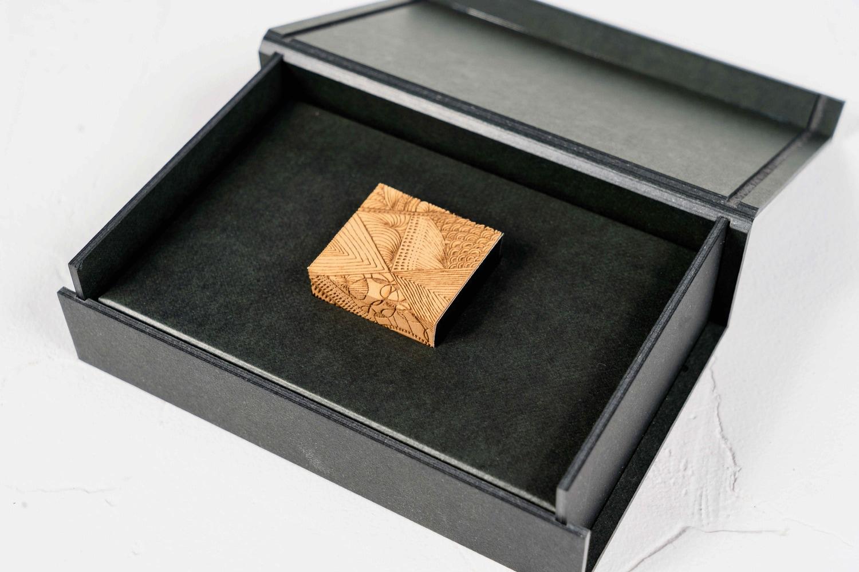 黒いギフト箱を開けると彫刻フセンが中央に入っている,monmecciの幾何学模様が彫り込まれた付箋,ハンドメイド文房具