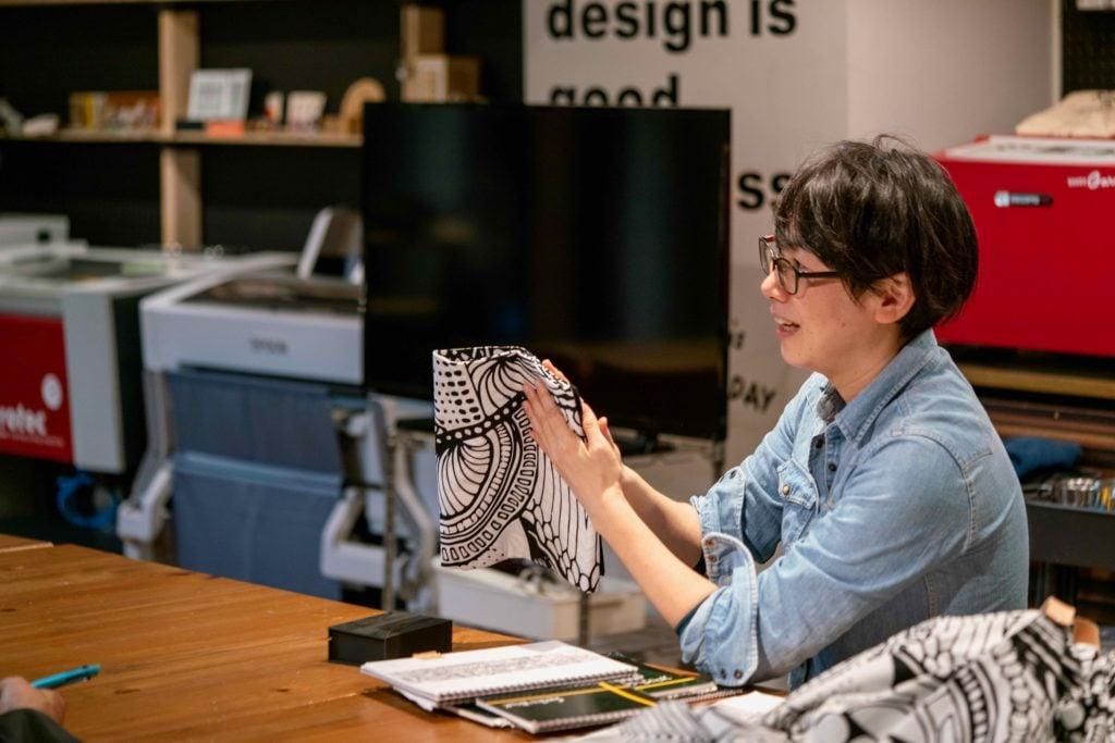 北海道札幌市のプロダクトデザインブランドmonmecci(モンメッチ),幾何学模様の風呂敷を手に持って説明するデザイナーの菊池さん
