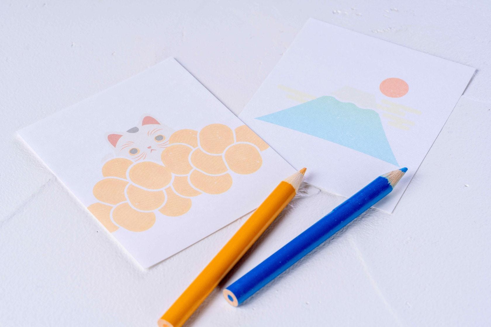 招き猫と富士山がデザインされたモリタのメモ用紙と青と橙の色鉛筆