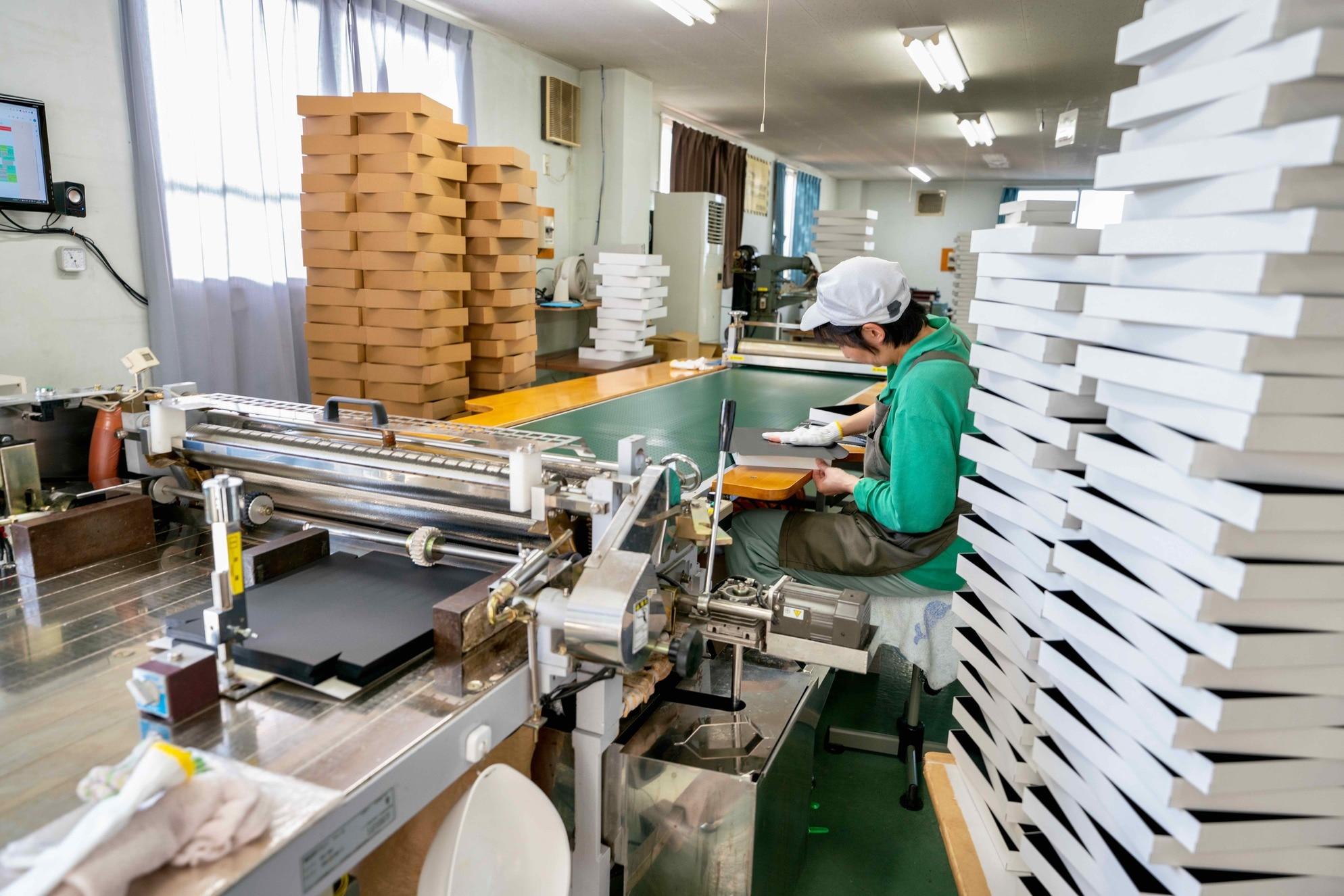オリジナルパッケージを製造中のモリタ株式会社の工房風景,紙箱に囲まれて制作