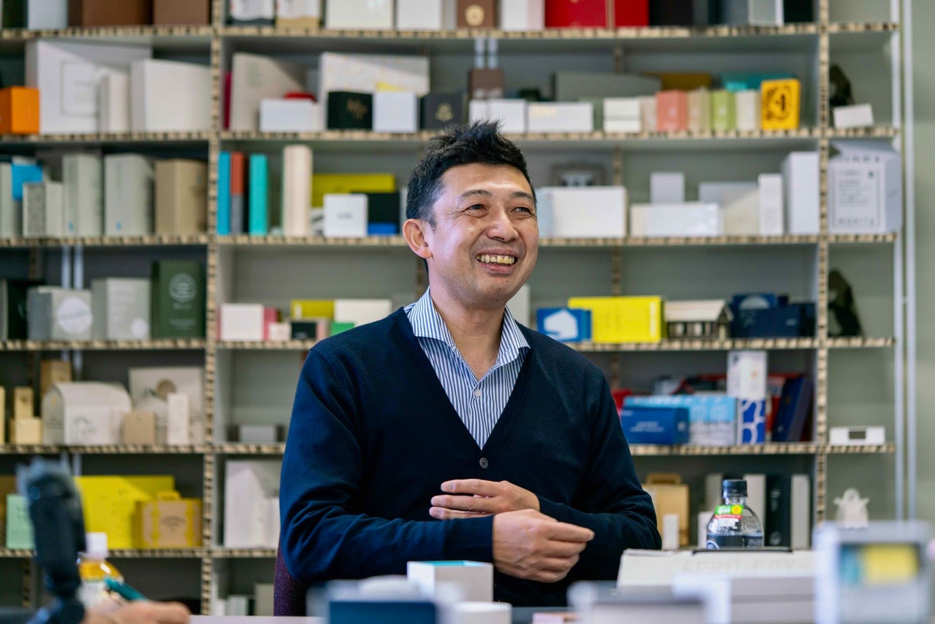北海道札幌市のモリタ株式会社,オリジナル制作の紙箱を背景に語る近藤社長