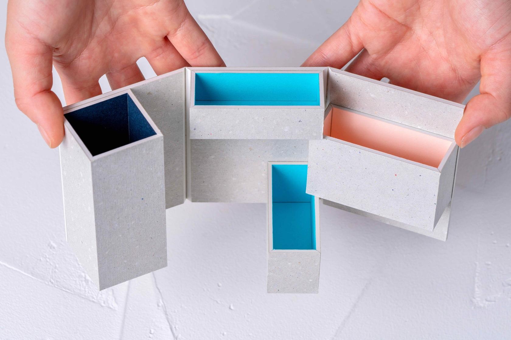 モリタのMiNiMuM Space BOX-1を手で開く,4つの収納スペースを持つ特殊加工の紙箱