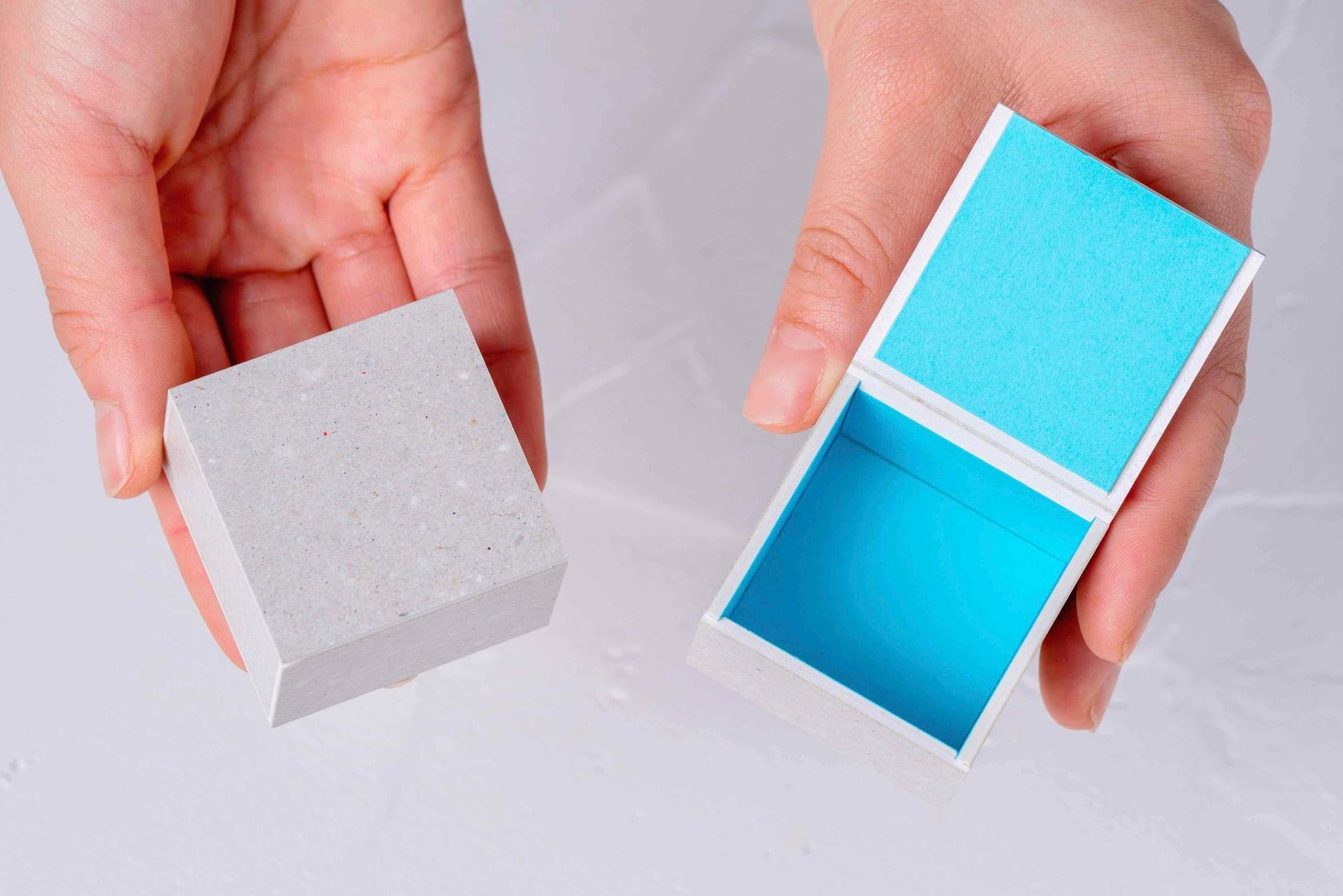 モリタのミニマムスペースボックス3を両手で持つ,手のひらに収まるサイズの小さな紙箱
