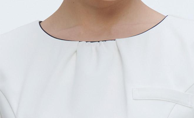 ノーカラーの衿元にはパイピングが入り、フロントのギャザーがやさしい雰囲気を演出しています
