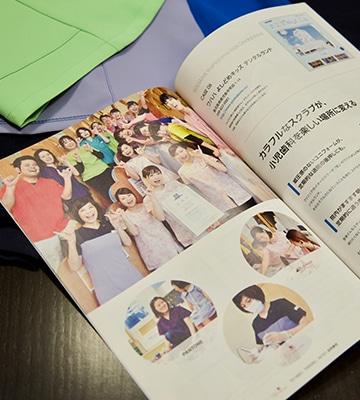 フォークが発行する、自社のスクラブが採用された病院の事例が掲載された冊子「現場の声」。働く人それぞれが自分好みのスクラブを着用している。