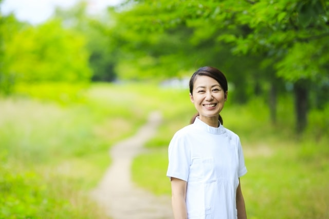 自然の背景に白衣の女性